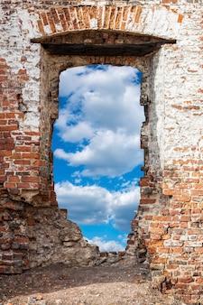 Старая кирпичная стена с отверстием против голубого неба с облаками. фото высокого качества