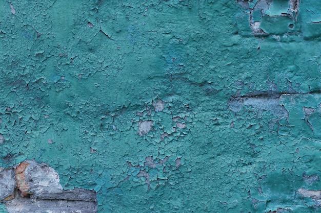 ひびの入った青いペンキコピースペースデザインやテキスト、横向きで古いレンガの壁