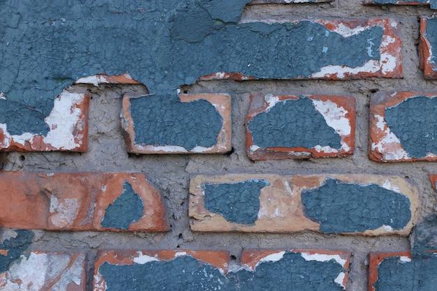 デザインやテキスト、水平方向のひびの入った青いペンキコピースペースを持つ古いレンガの壁