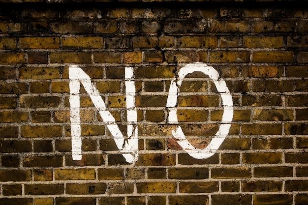 Noという言葉が書かれた古いレンガの壁