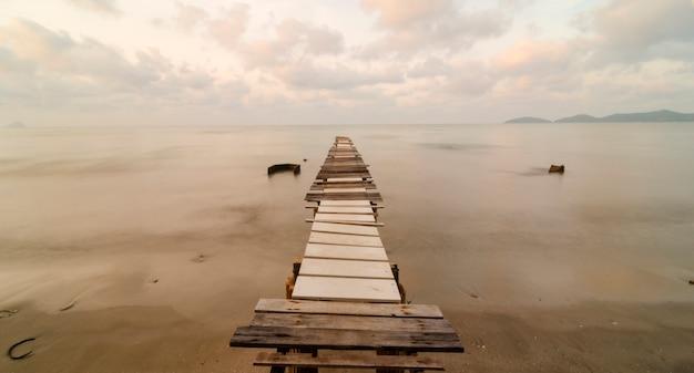 Old bridge during sunrise at tropical sea, thailand