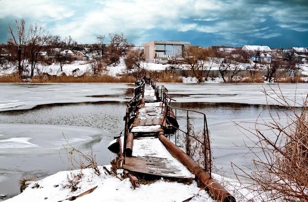 冬の村の近くの川の古い橋