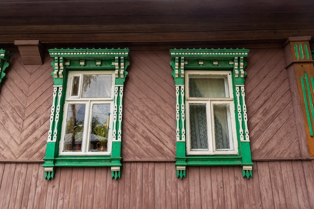 Old bright facade of traditional russian rural house made of wooden logs with cute decorated platbands on windows at countryside on nice summer day.