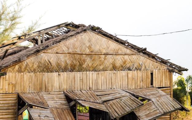 Старый сломанный заброшенный деревянный и бамбуковый дом