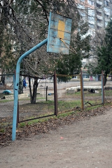 Старое сломанное баскетбольное кольцо на поле