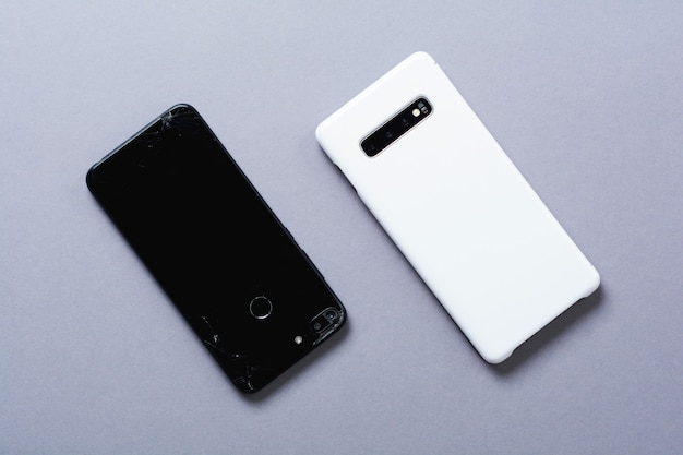 Old broken black and new white smartphones on gray background. the concept of recycling phones and technologies. top view.