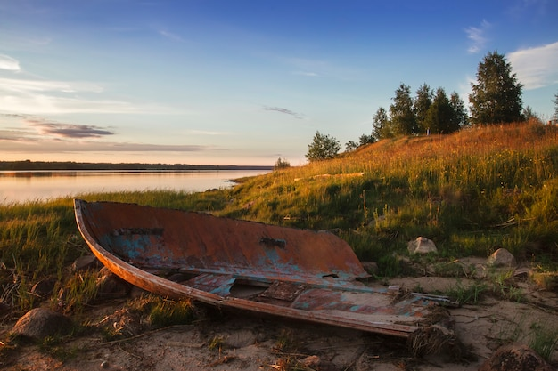 Old broken boat on the shore of the lake at sunset