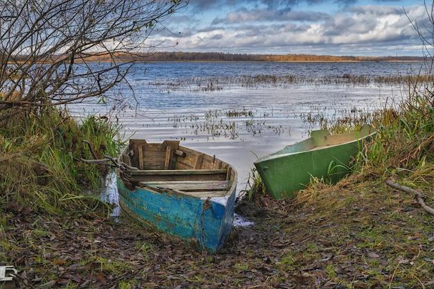 Старые сломанные лодки на берегу небольшого озера