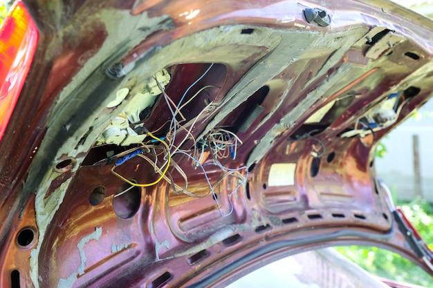 Старая сломанная машина. ржавый багажник. электрические провода нуждаются в ремонте.