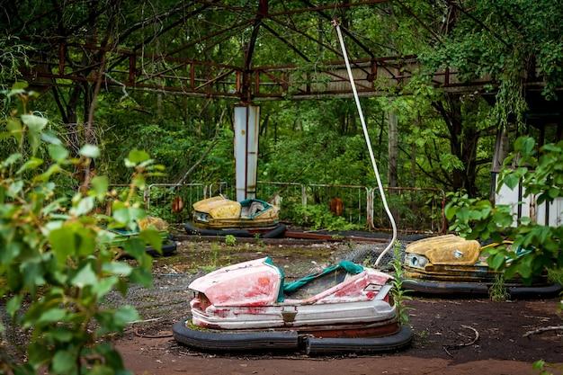 Старые сломанные детские электромобили в парке развлечений, парке отдыха в городе припять. зона отчуждения чернобыльской аэс