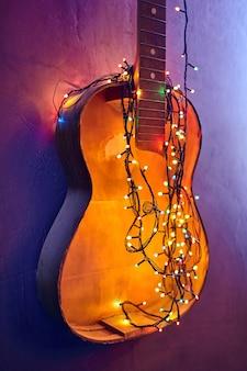 古い壊れたギターには、輝くガーランドが飾られています。クリスマスのインテリア。黄色の新年の電球