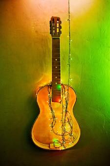 Старая сломанная гитара украсила светящуюся гирлянду на стене. рождественский декор интерьера. новогодние лампочки