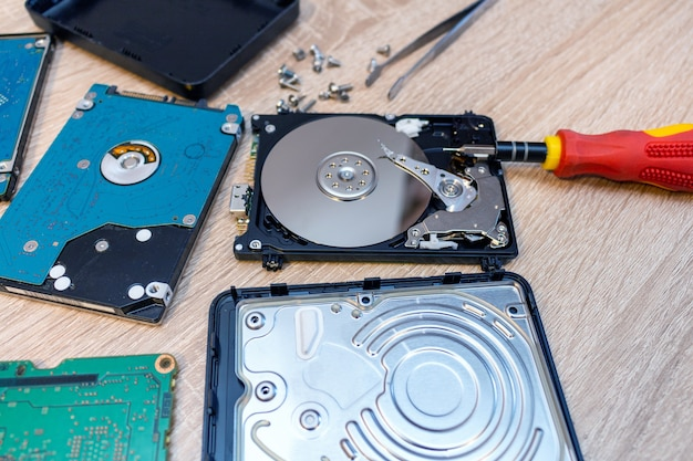 Old broken hard disk drives composition in a repair recovery service concept close up selective focus