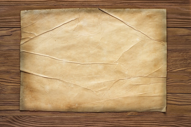 Old broken horizontal sheet of paper on brown wooden board