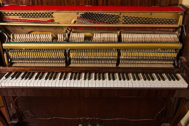 Старое сломанное пианино, стоящее у стены