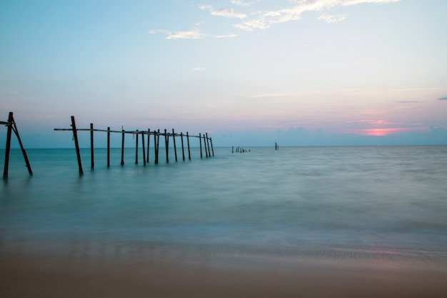 Old broken pier on the beach at the sunset background.
