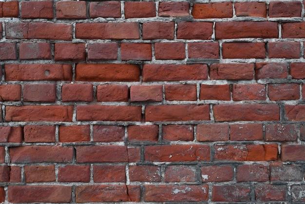 外の赤レンガの古い、壊れた壁、クローズアップ。テクスチャの背景