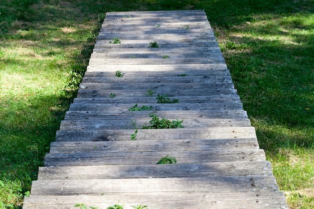 썩은 계단의 오래된 깨진 나무 계단 부분, 계단이 세워진 언덕에 클로즈업