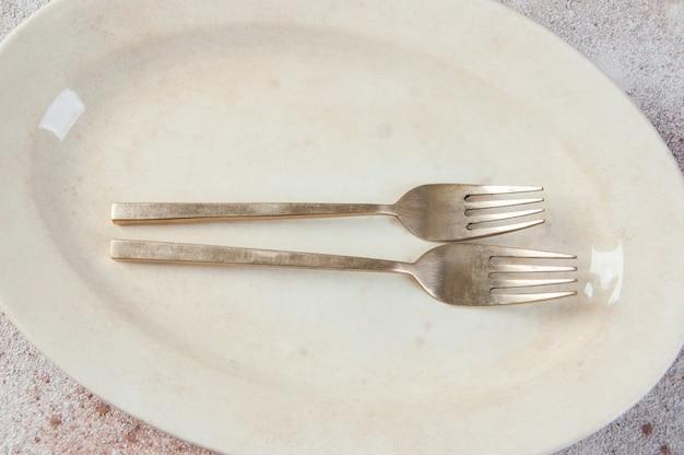 Старые бронзовые вилки на винтажное блюдо