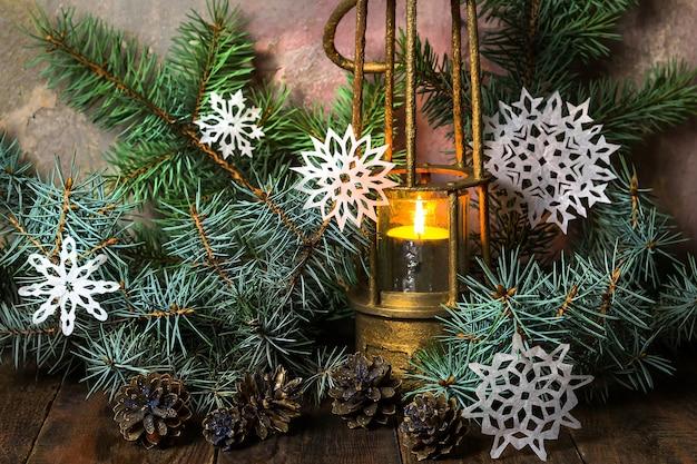 Старая бронзовая лампа с горящей свечой на деревянном столе в ветвях елки