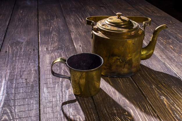 Old bronze teapot with a cup on the table
