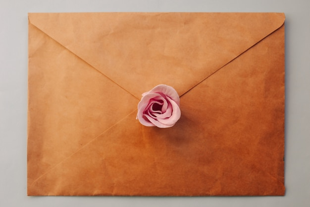 An old brown envelope, pink rose flower on a blue background. minimal flat lay