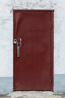 Old brown painted iron door with metal locks. close-up. vertical.