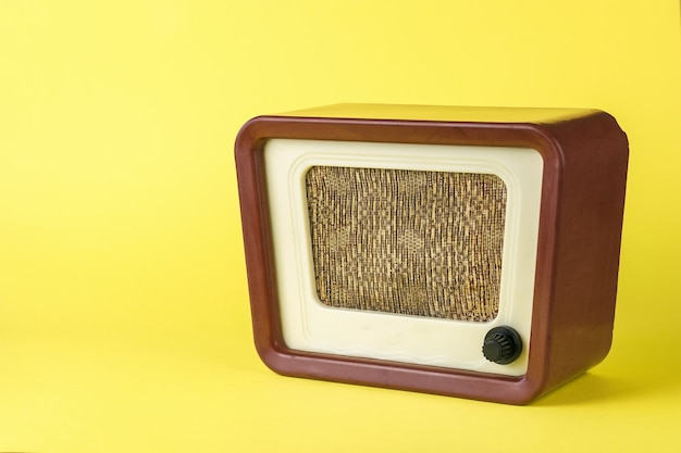 Old brown radio on yellow background. radio engineering of the past time. retro design.
