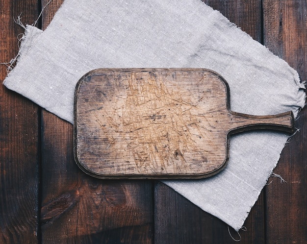 Старая коричневая прямоугольная деревянная кухонная разделочная доска и серая льняная салфетка на столе, вид сверху