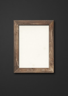 Old brown rustic wooden picture frame hanging on a black wall. blank mockup template