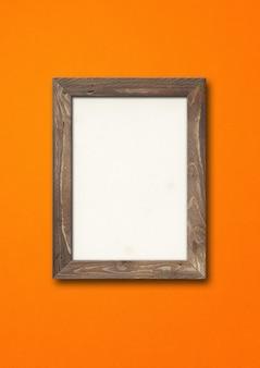 オレンジ色の壁に掛かっている古い茶色の素朴な木製の額縁