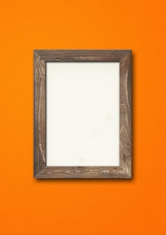 Old brown rustic wooden picture frame hanging on an orange wall