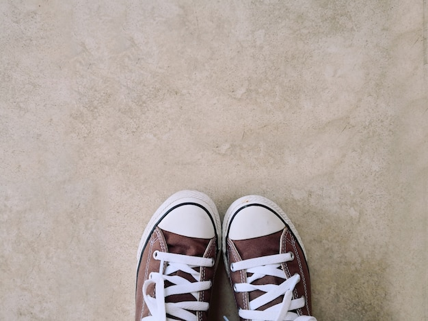 Old brown sneakers, placed on a cement background.