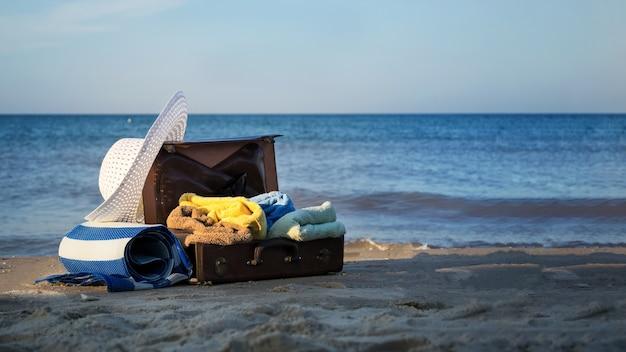 Старый коричневый чемодан на берегу моря. свободное место