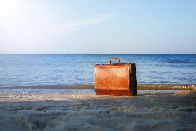 Старый коричневый чемодан на берегу моря. винтажный чемодан