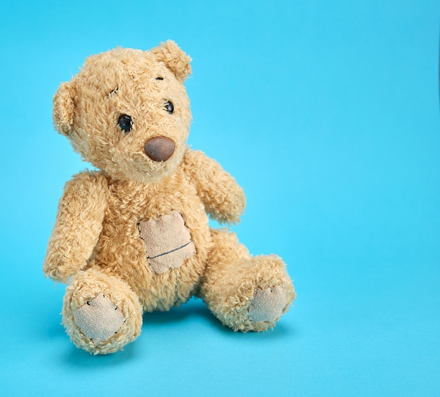 Old brown teddy bear on a blue  background