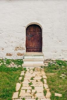 Старая коричневая деревянная дверь на белой кирпичной стене с каменной дорожкой и травой