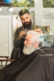 Old brutal customer cutting hair at barbershop