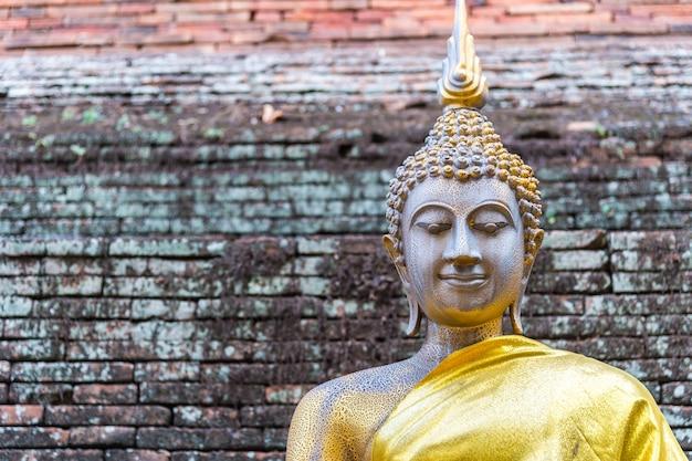 Статуя старого будды с кирпичной стеной фона