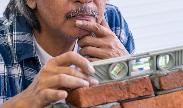 Old builder職人はレンガの壁を平準化します。