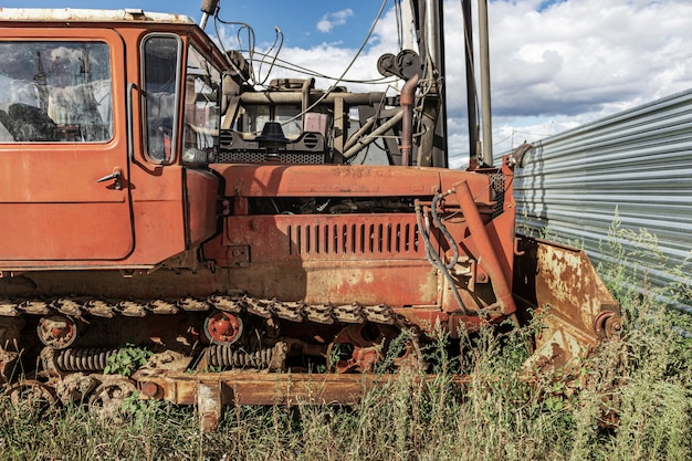 An old bulldozer machine with a heavy bucket. earth-moving harvester with caterpillars at a construction site. close-up. construction heavy machinery.