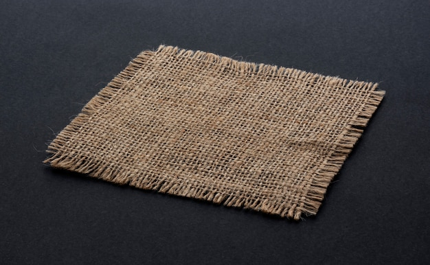 Old burlap fabric napkin on black background
