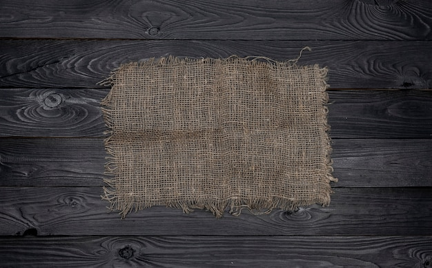 Old burlap fabric napkin on black wooden background, top view