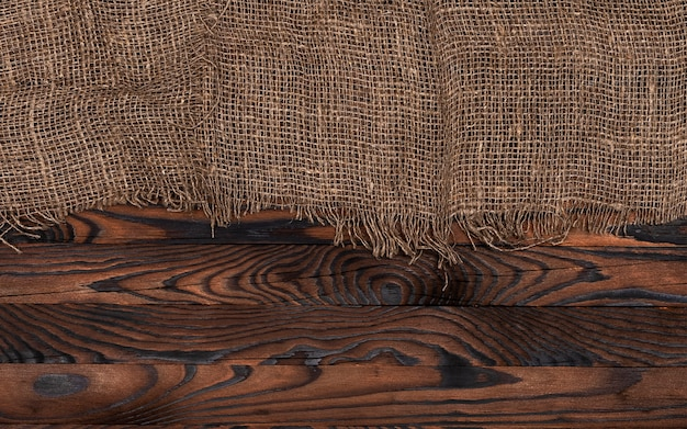 Old burlap fabric napkin on brown wooden background, top view