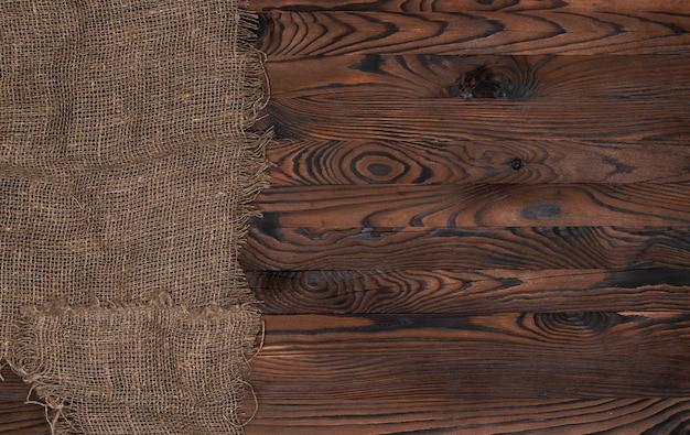 Старая салфетка ткани мешковины на коричневой деревянной предпосылке, взгляд сверху
