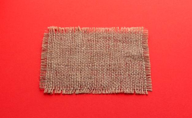 Old burlap napkin on red color background