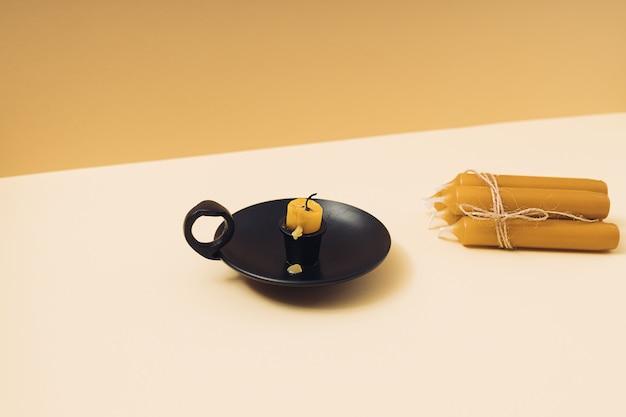 검은색 빈티지 촛대에 있는 오래 된 탄 왁스 양초와 기하학적 노란색 배경에 새 양초 더미.