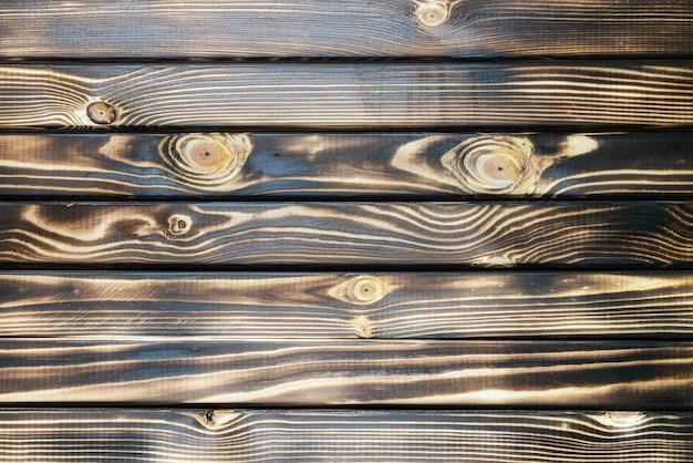 水平板と古い焦げた木の板ダークブラウンのテクスチャ背景。フラットレイのクローズアップビュー。