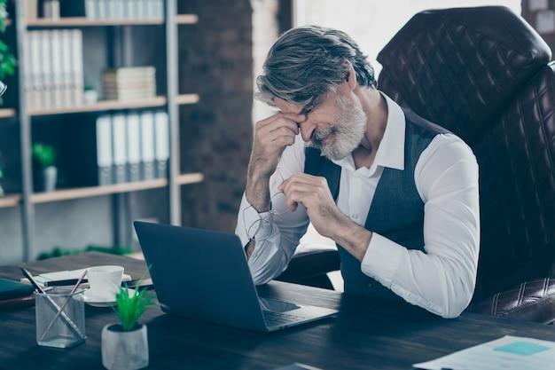 Старый бизнесмен сидит на стуле с головной болью в офисе