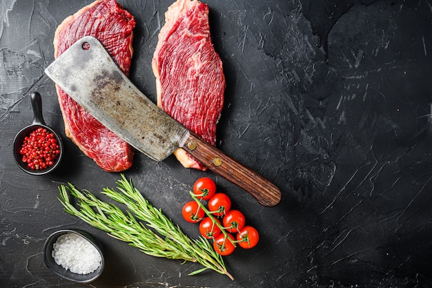古い肉屋がローズマリー、ペッパーコーン、塩を添えた生のピカンハビーフステーキを割る